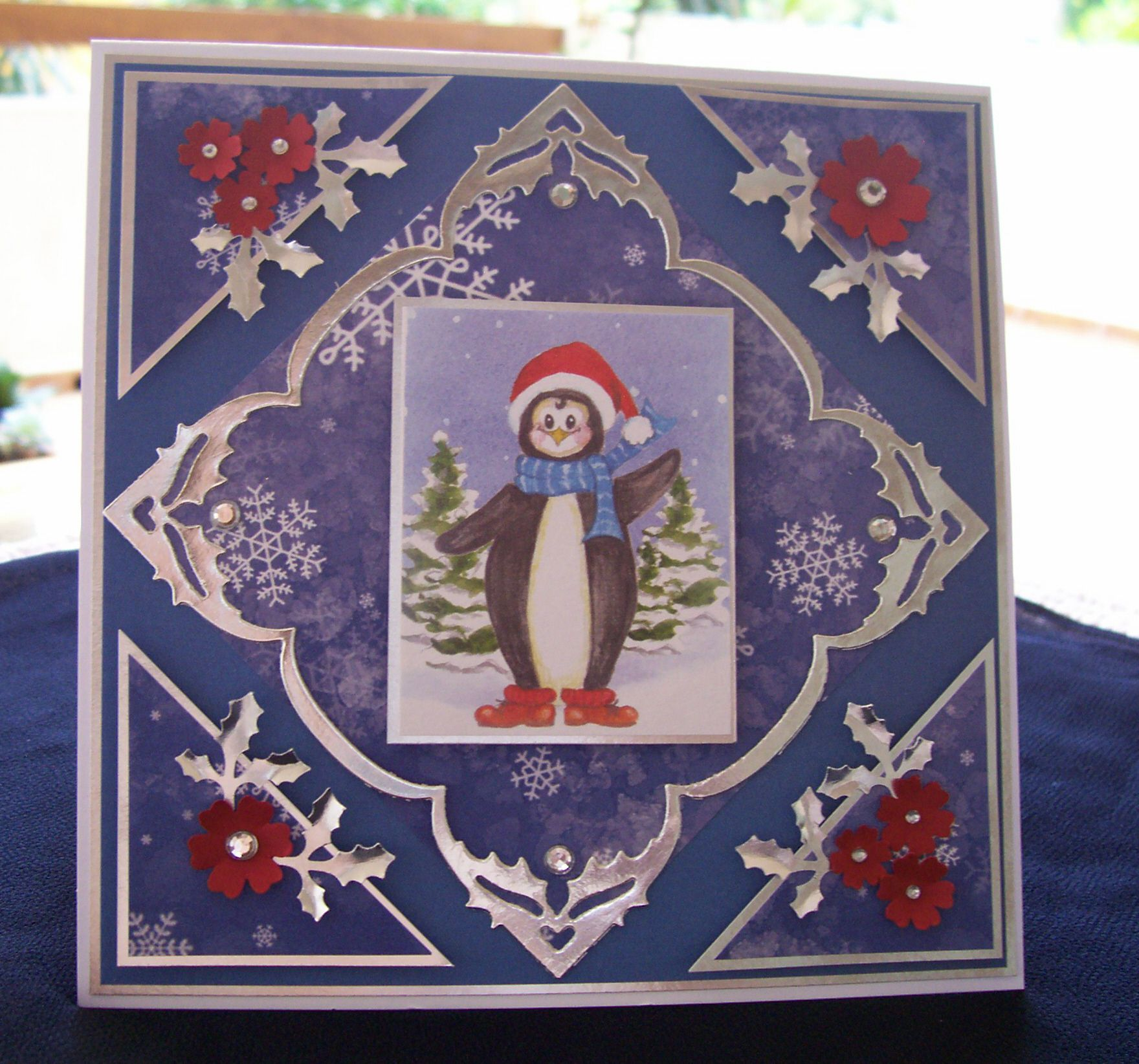 Silver and blue Christmas card with accents of red in the image and flowers.