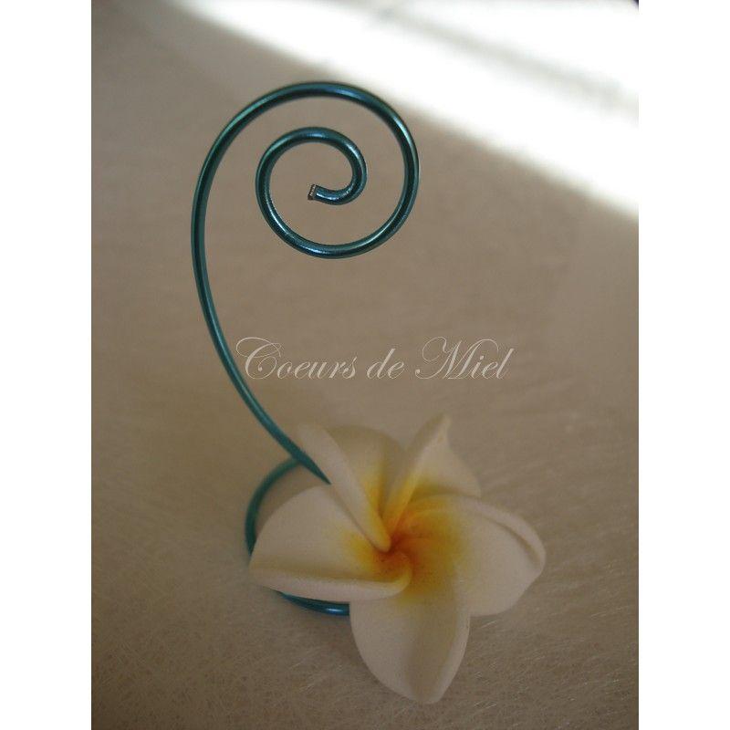 Le marque place NOAM pour une décoration mariage exotique.  DESCRIPTION : Frais et lumineux, ce marque place sera idéal pour un mariage au thème exotique. Réalisé à partir d'une fleur de frangipanier, ce marque place maintiendra le prénom de votre invité par l'arabesque.