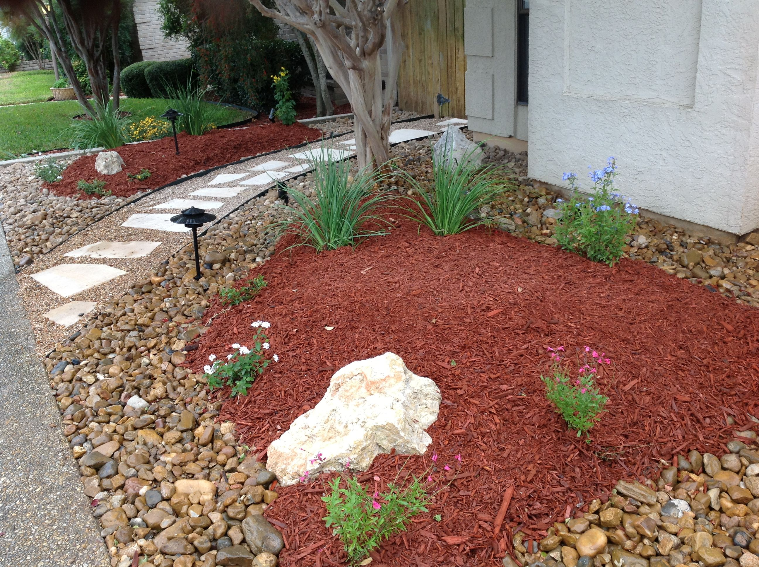 Rocks against paths bark mulch in planting area stepping for Small red rocks for landscaping