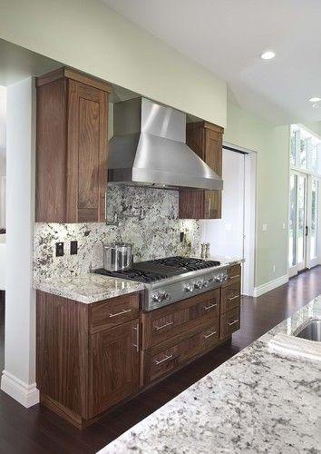 Dark floor, walnut cabinets, light granite counter ...