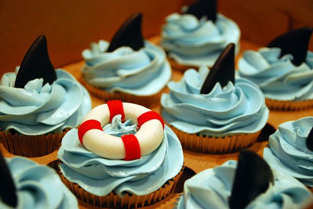 Shark cupcakes. Need to make these with some good old-fashioned skull cakes and jolly rogers.