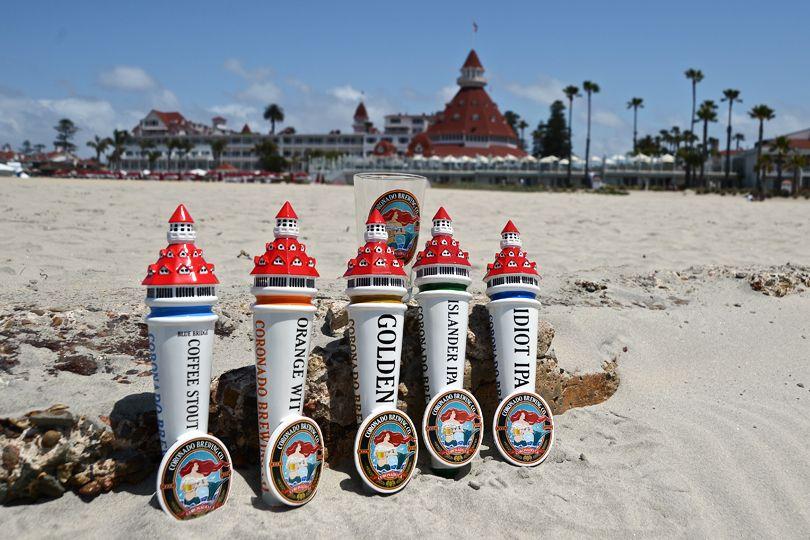 Coronado Brewing Company tap handles plugged into the warm sand in front of the Hotel Del Coronado's beach.
