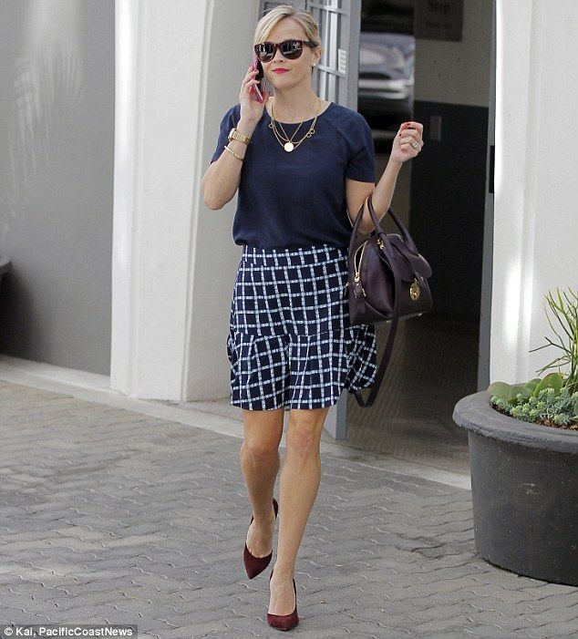 Business chic: Reese Witherspoon looked charming in a navy blouse and flowing skirt as she...