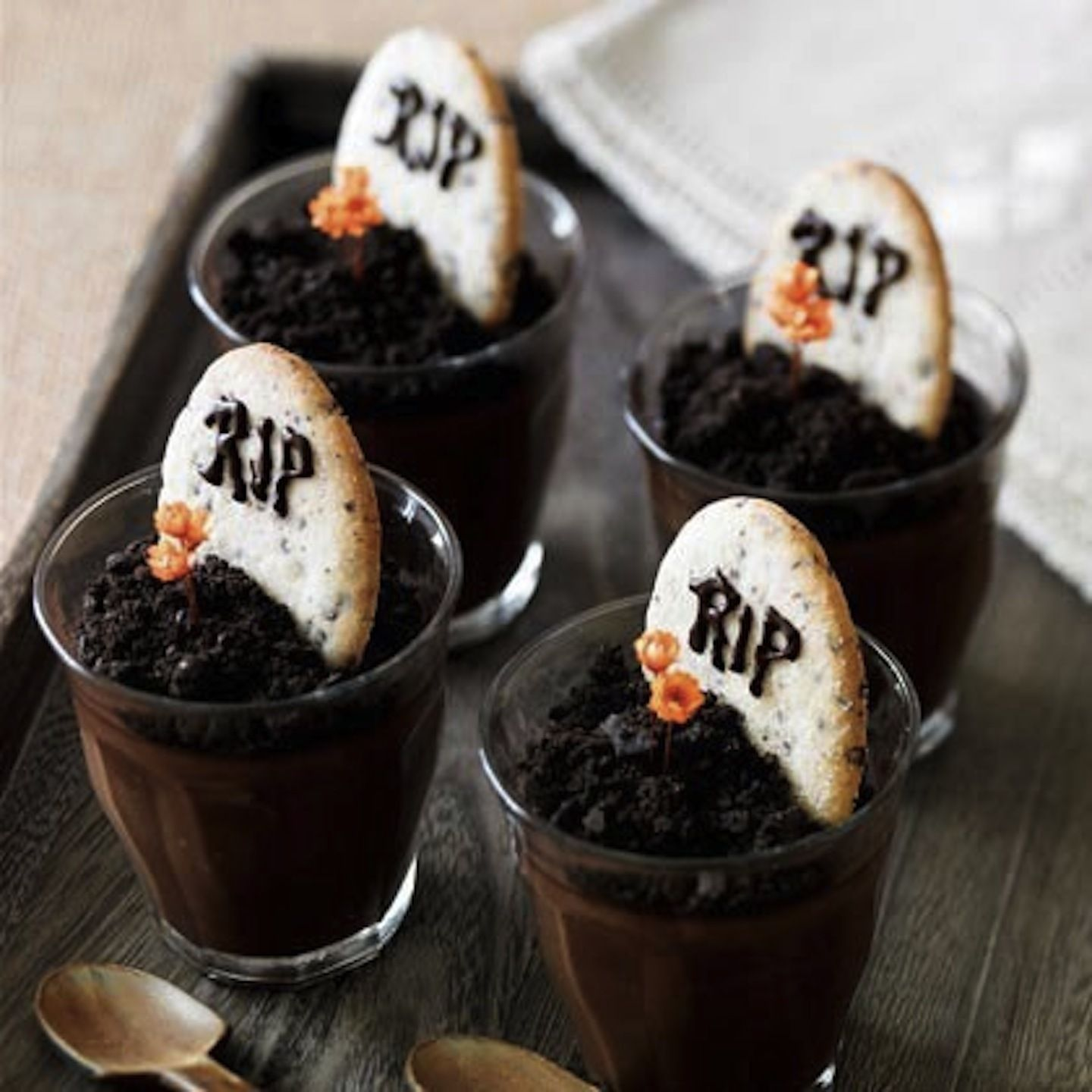 Graveyard Pudding  Turn your chocolate pudding cups into miniature graveyards! Just throw some dirt on top (crumbled chocolate cookies, Oreos are a good choice!) and a cookie tombstone. Pepperidge Farm Milanos work well, they are about the right size and have that tombstone shape. Add a frosting RIP on the headstones and toss in some decorative flowers for the full effect.