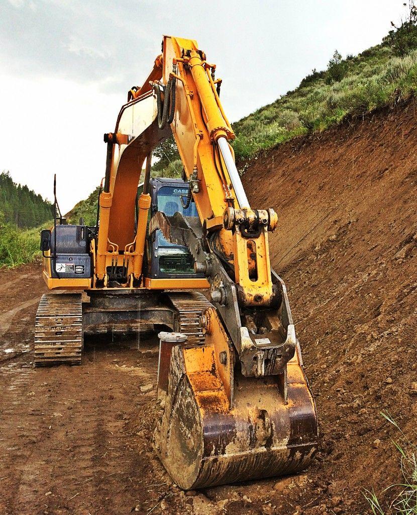 Excavator Digging Near a Hill