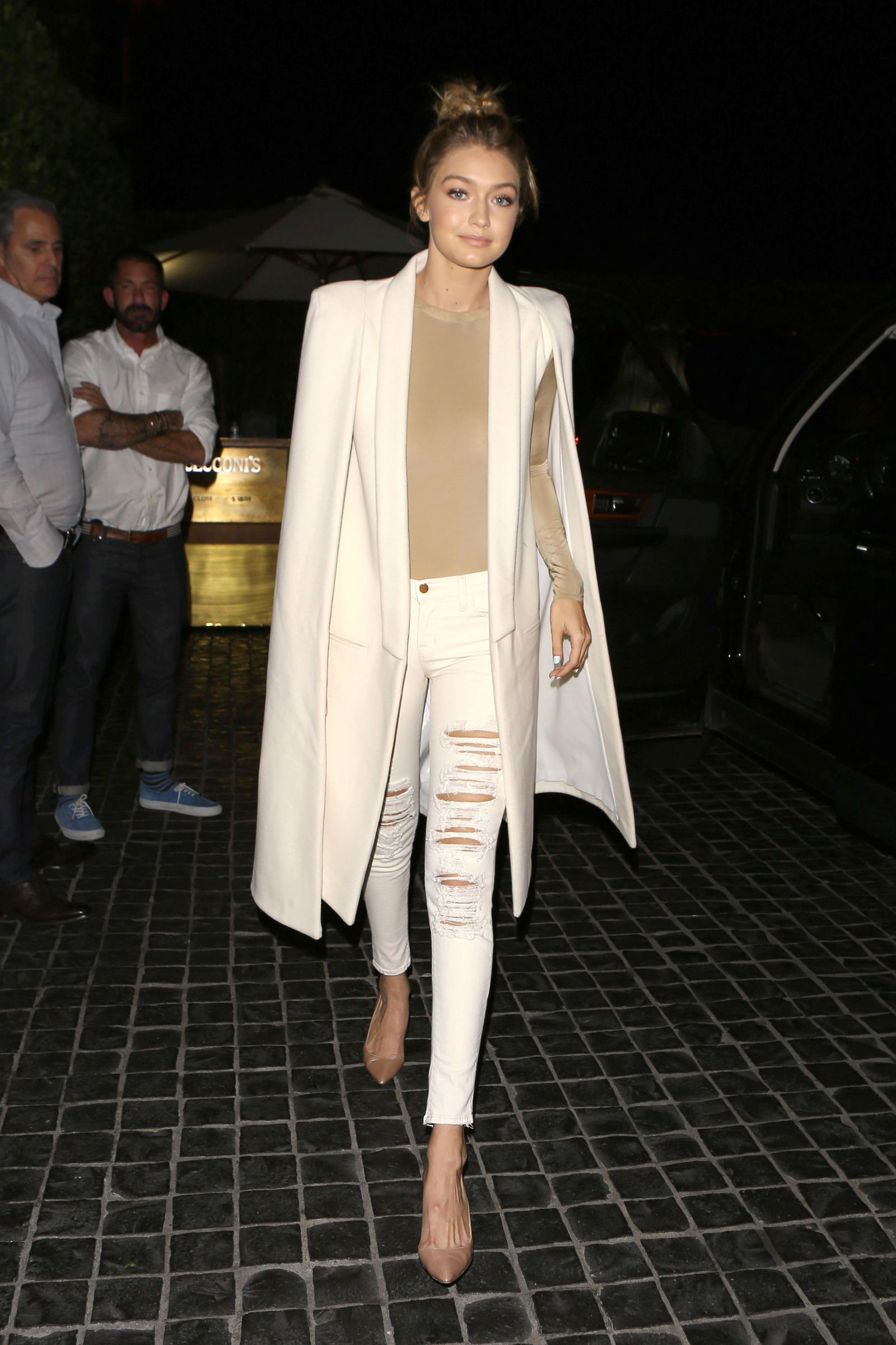 For a dinner date with the Kardashians in L.A., the model steps out in a white Olcay Gulsen coat paired with distressed denim, a nude bodysuit and matching heels.    - HarpersBAZAAR.com