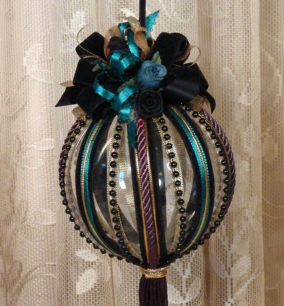 Hanging Victorian Ornament This is a beautifully decorated black & teal hanging Victorian ornament. The ornament is clear acrylic but has the appearance of glass. It has been heavily decorated with teal and black velvet ribbon and pearl beads, along with pearl beads, cording, trim and fringe. The ornament is great to hang from a sconce, chandelier or Christmas tree. Hand decorated by me and is one of a kind. Measures approximately 4 in diameter x 12 long. If you have any questions, ...