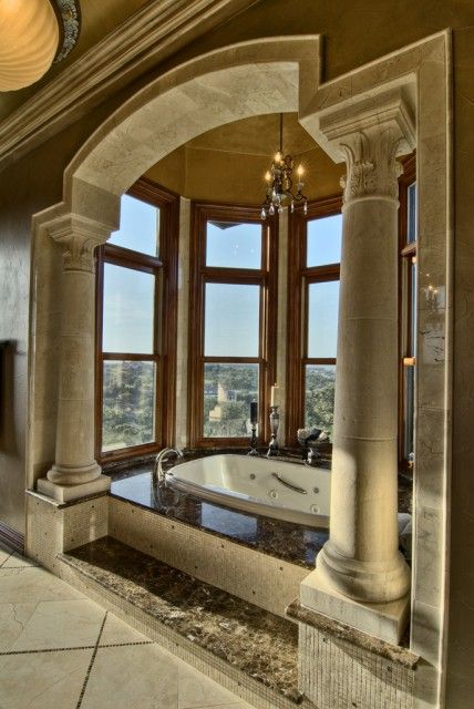 A whirlpool soaking tub is set into an alcove of windows, framed by ...