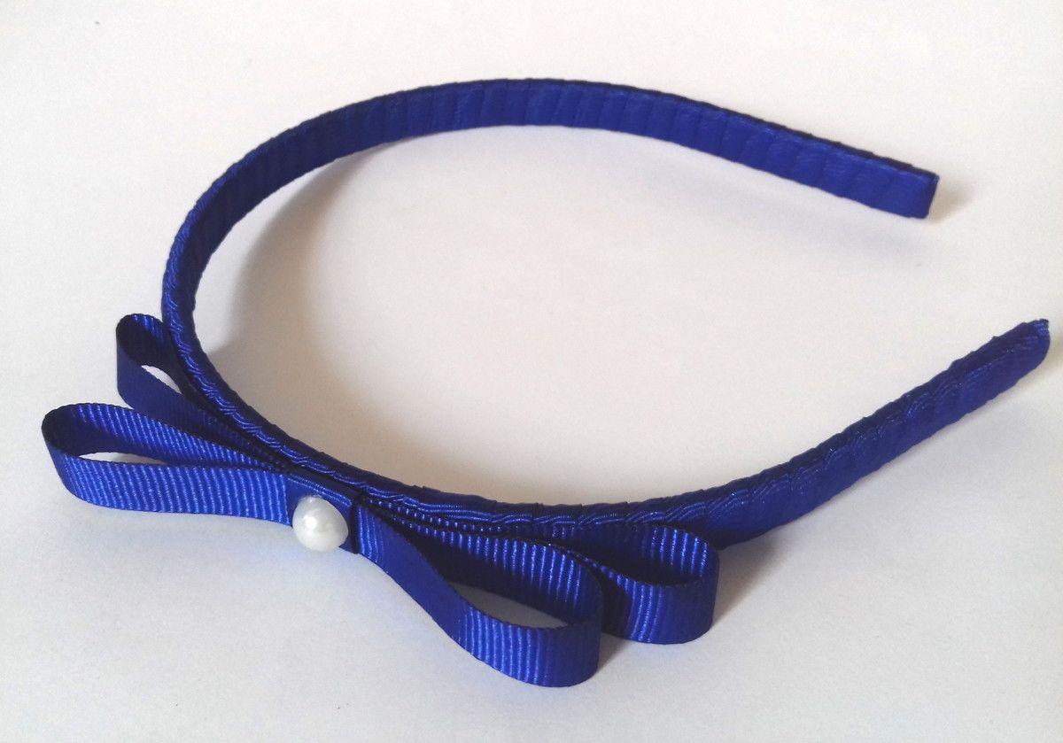 Tiara revestida em fita de gorgurão azul marinho com detalhe em pérola.  Laço com aproximadamente 10 cm.    *A tiara pode ser feita em outras cores e com outros detalhes de sua preferência. Entre em contato com a gente!