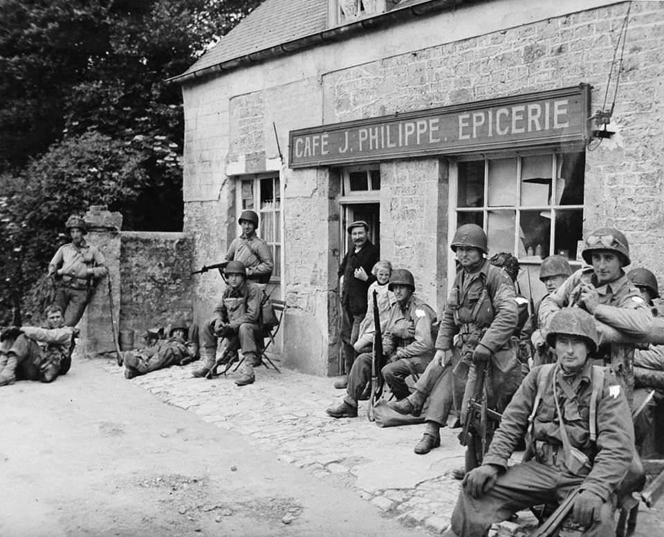 GI's of 22nd Infantry Regiment, resting for few moments outside a cafe in Baudienville, village lies just under 2.5 Km NE of Sainte-Mère-Église, Normandy, France. 7 June 1944 (© WWII Archives)