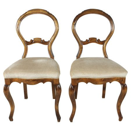 Highlighting iconic Louis-style silhouettes, these vintage French walnut wood side chairs showcase balloon backs and cabriole legs.