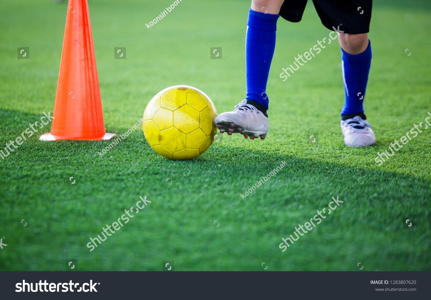 Kid soccer player control ball around cone maker for