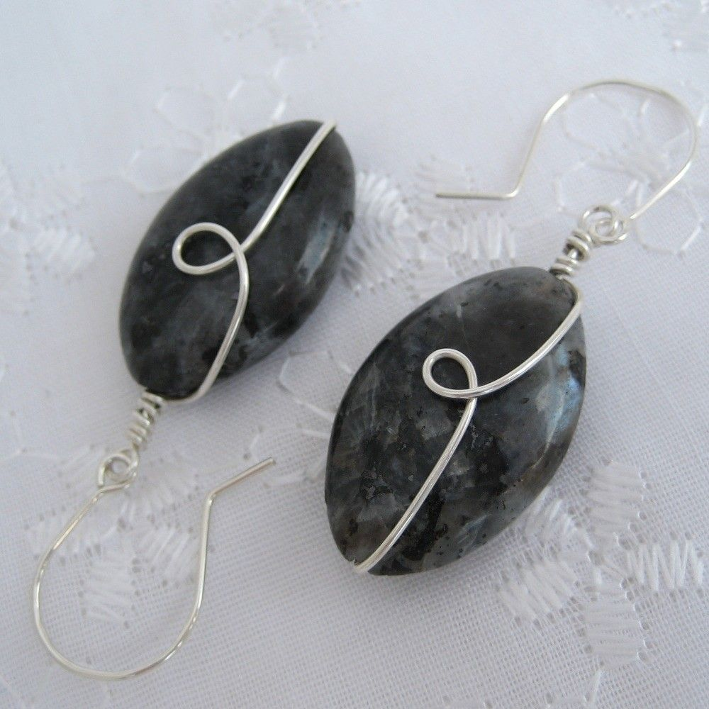Light-blue reflections and flecks of black are seen throughout these lovely Larvikite spindle beads. Wrapped with sterling silver-filled wire, decorated with a swirl. Swings from hand-formed sterling silver ear wires. Measures 1 3/4 inches in length from top of ear wire to bottom of bead. These are made promptly to order and shipped quickly. They will not be the exact earrings in the photo, but will be remarkably similar to the pair shown.