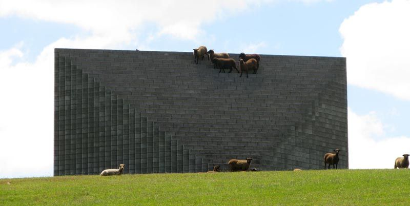 """My favorite sculpture on Gibbs Farm in New Zealand, if only because the sheep find it so entertaining. The idea of shooing sheep off your multi-million dollar art installation does not fail to amuse me for a second. This being Sol LeWitt's """"Pyramid"""" and owned (art, farm, sheep) by Alan Gibb, one of New Zealand's richest citizens."""