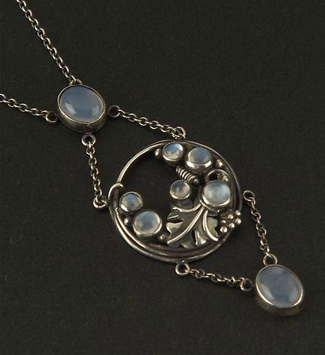 Dorrie Nossiter (in the style of). Silver and moonstone pendant, the circular frame with cabochons, a leaf, tendrils and beads, with a cabochon drop below and divider above. 2.8 cm diameter on a chain 45 cm long. This is similar to a pendant without the drop below and divider above featured http://www.dorrienossiter.co.uk/designs/plant-forms-and-design/natural-forms.html. Sold by Dreweatt Neate.