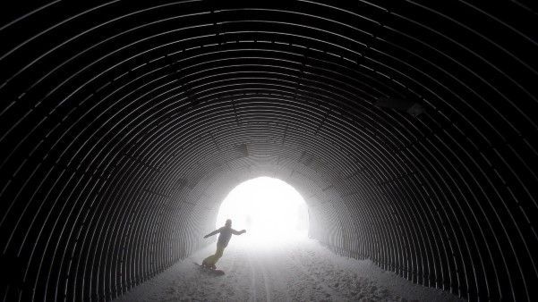 A Snowboarder Goes Through A Tunnel Near The Alpine Skiing Training Slopes