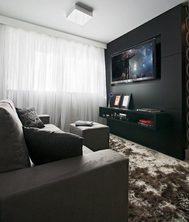 O Home theater de parede preta e móveis em tons de cinza é aconchegante, sofisticado e masculino