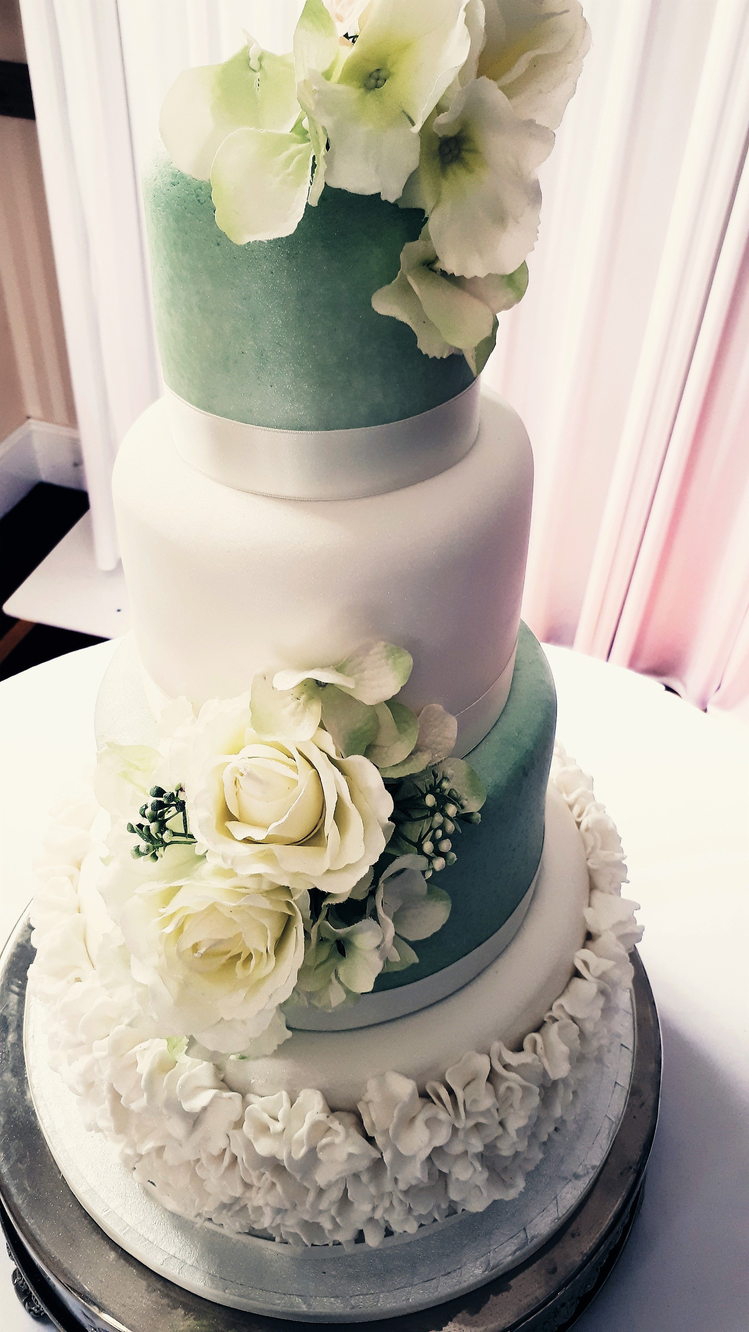 Four tier fondant covered wedding cake decorated with a