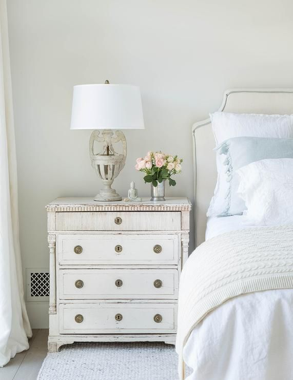 Chic Off White Bedroom Features An Headboard With Blue Piping On A Bed Dressed In Soft Linen Bedding As Well Ruffled Shams Placed