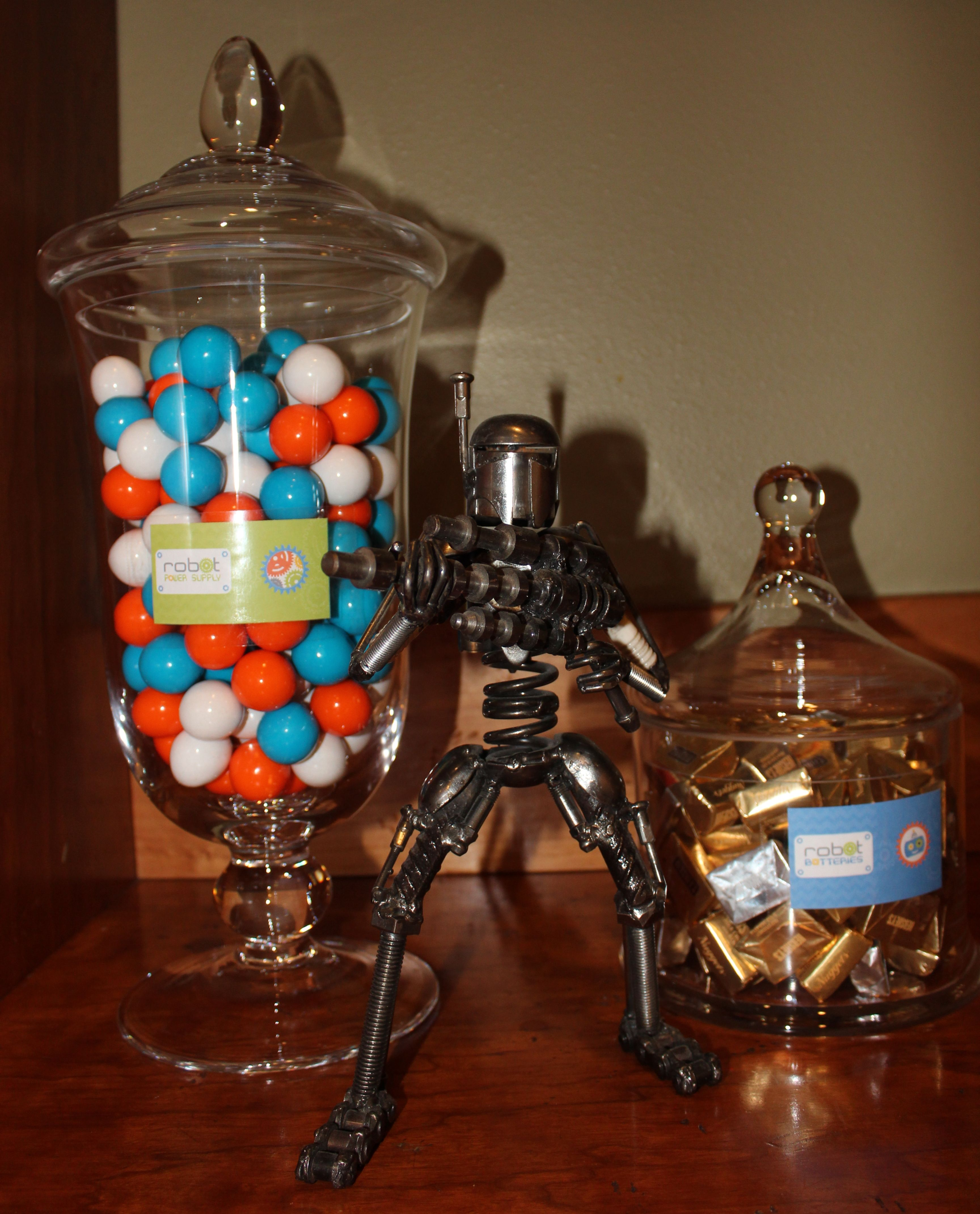 Robot Power Station / Power Supplies (orange, blue and white gumballs) and Batteries (mini Hershey bars in gold and silver wrappers) guarded by a mini robot. - Robot Birthday Party #robot #robotparty #candy #dessert