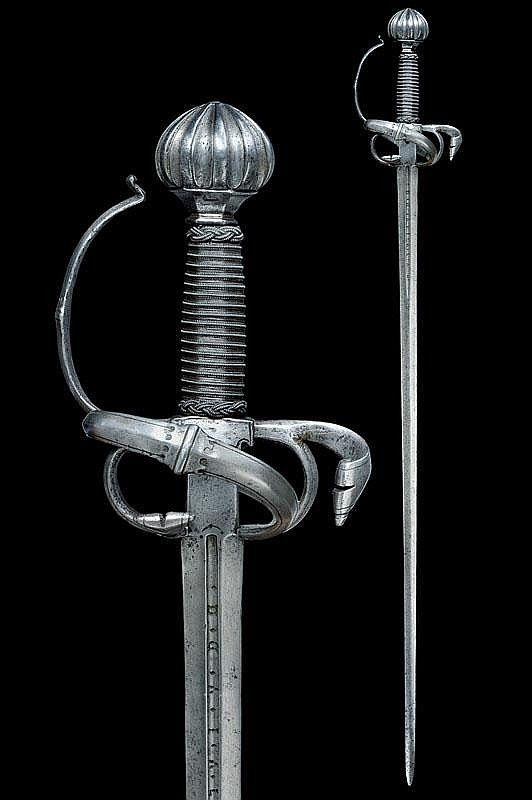"""A fine rapier Straight, double-edged blade of lenticular section, grooved at the first part signed """"TOMAS D'AIALA""""; rectangular tang, elegant hilt with lower-side ring, chiselled with curls, outlined at the borders, deeply grooved pommel; wooden scabbard with iron wire binding and moor's heads. dating: third quarter of the 16th Century provenance: Southern Germany condition report: very good- by Czerny's International Auction House"""