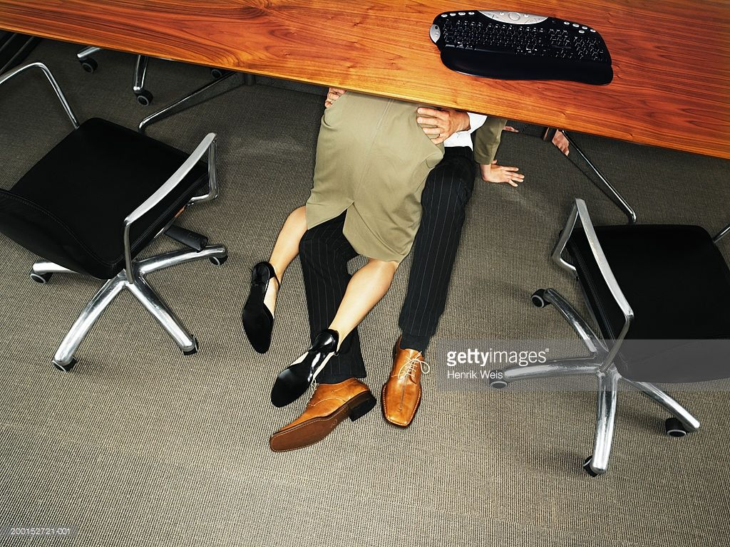 Business couple embracing under desk elevated view