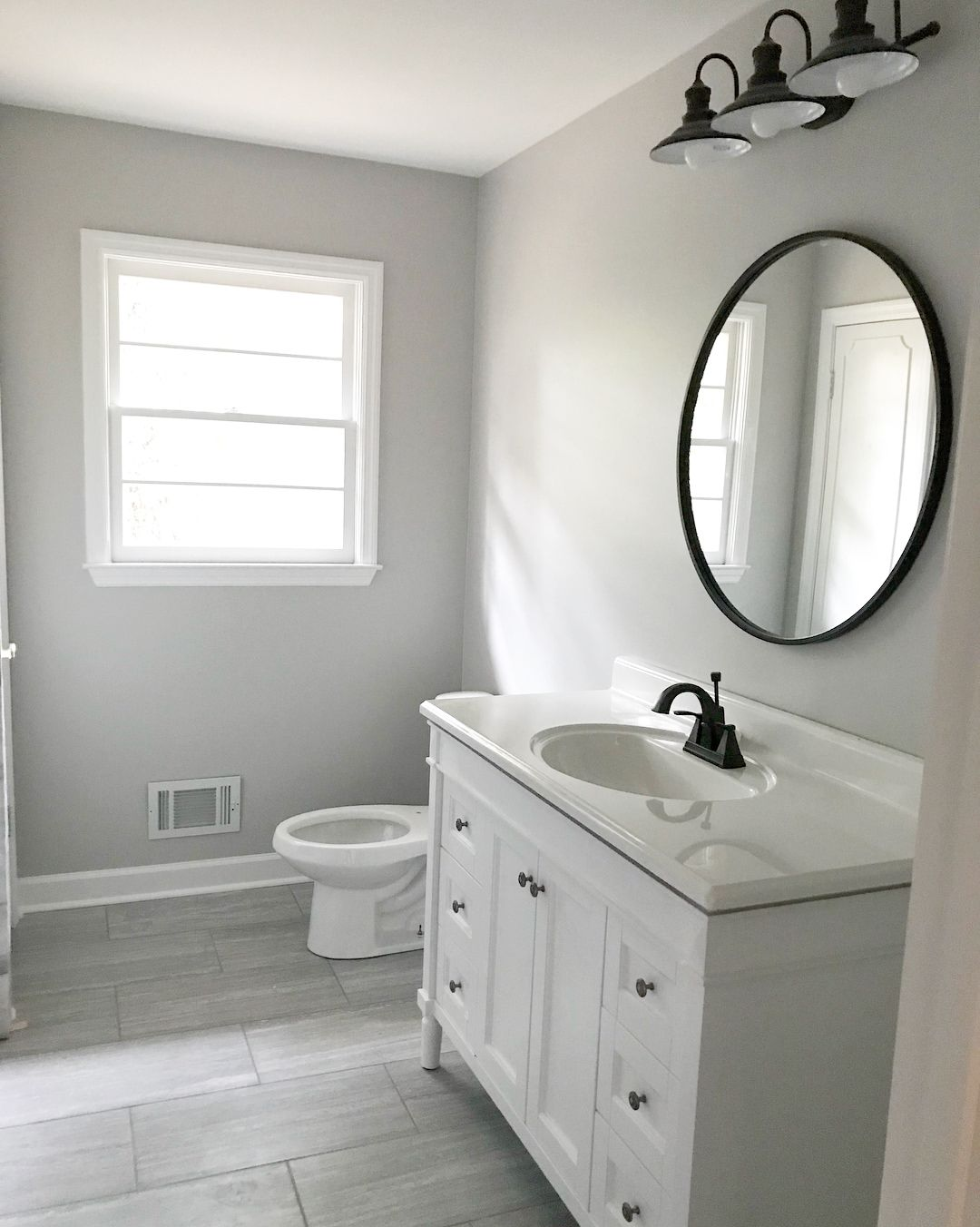 White And Gray Bathroom With Black Circle Mirror White Cabinets With Black Hardware Badkamer