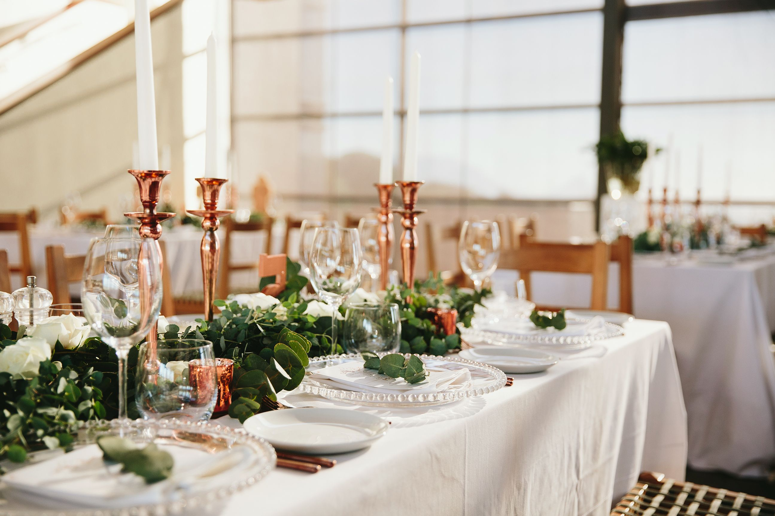 Greenery runner with glass underplates and rose gold decor items