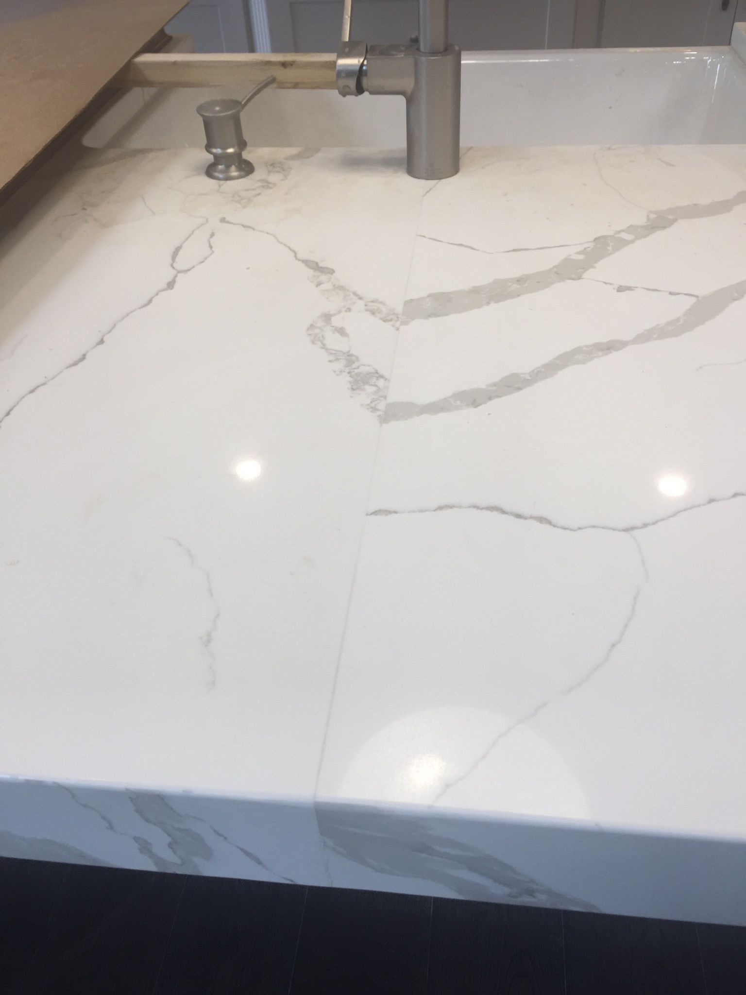 Calacatta laza quartz seam in island solid surface for Seamless quartz countertops