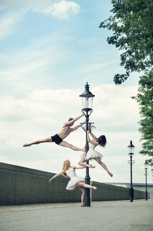 Ballerinas on a lamp post.    (Click through for more ballerina photos from Benjamin Von Wong!)
