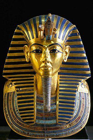 Maschera (funeraria) di Tutankhamon. Nuovo Regno. Realizzata in oro, gemme e vetri colorati.  Ritrovata nella Valle dei Re, Tebe (odierna Luxor). Conservata al Museo egizio del Cairo