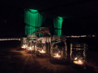 Mason Jar centerpieces with lighted backdrop. Rustic wedding. Uniquely Yours Wedding Design