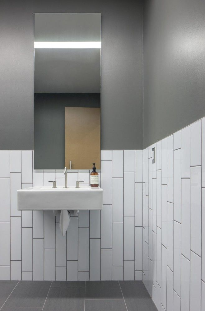 Men 39 s bathroom in commercial space white subway tile for Commercial office bathroom ideas