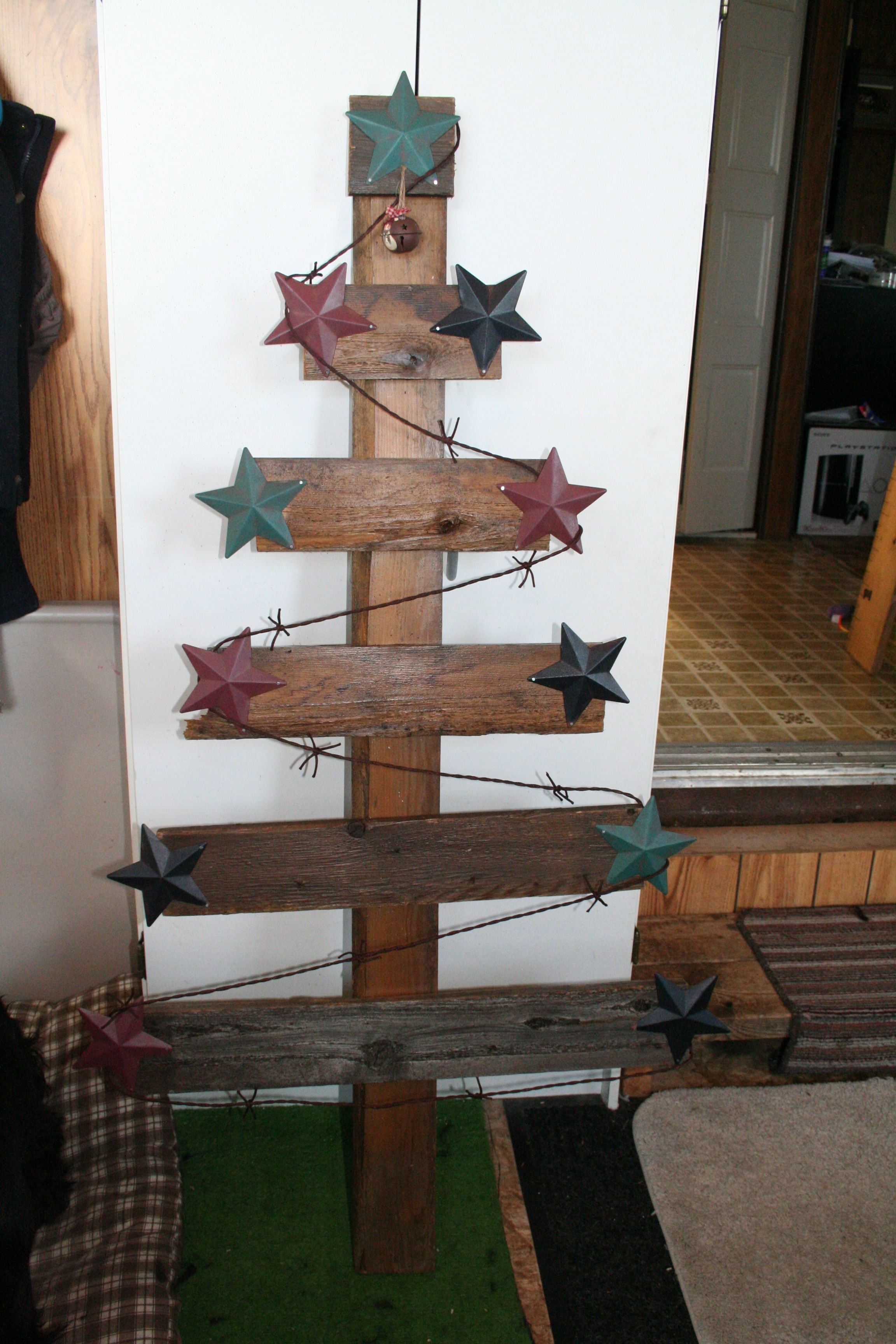 Used one x four boards cut at different lengths and screwed them to another 1 x 4. Added metal stars and rope barb wire. Hanger on back to hang on wall