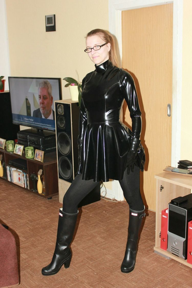 ca7384a87c Amateur blonde in black latex skater dress and high heel rubber boots in  the living room