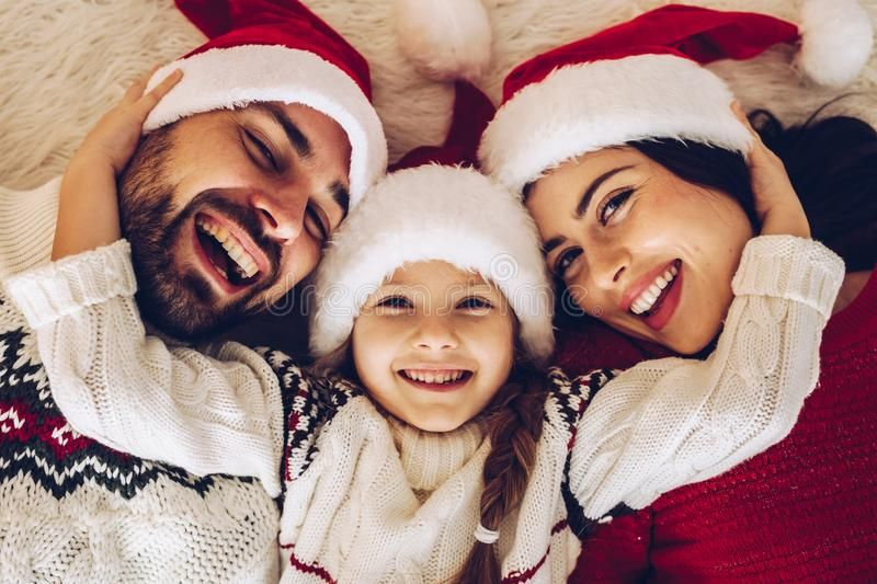 Christmas Family Happy Mom Dad And Little Daughter On Santa Cla Us Hats Lying Spon Daught Christmas Photoshoot Christmas Family Photos Family Christmas