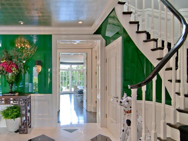 All white stairs lead down into a vibrant green room!
