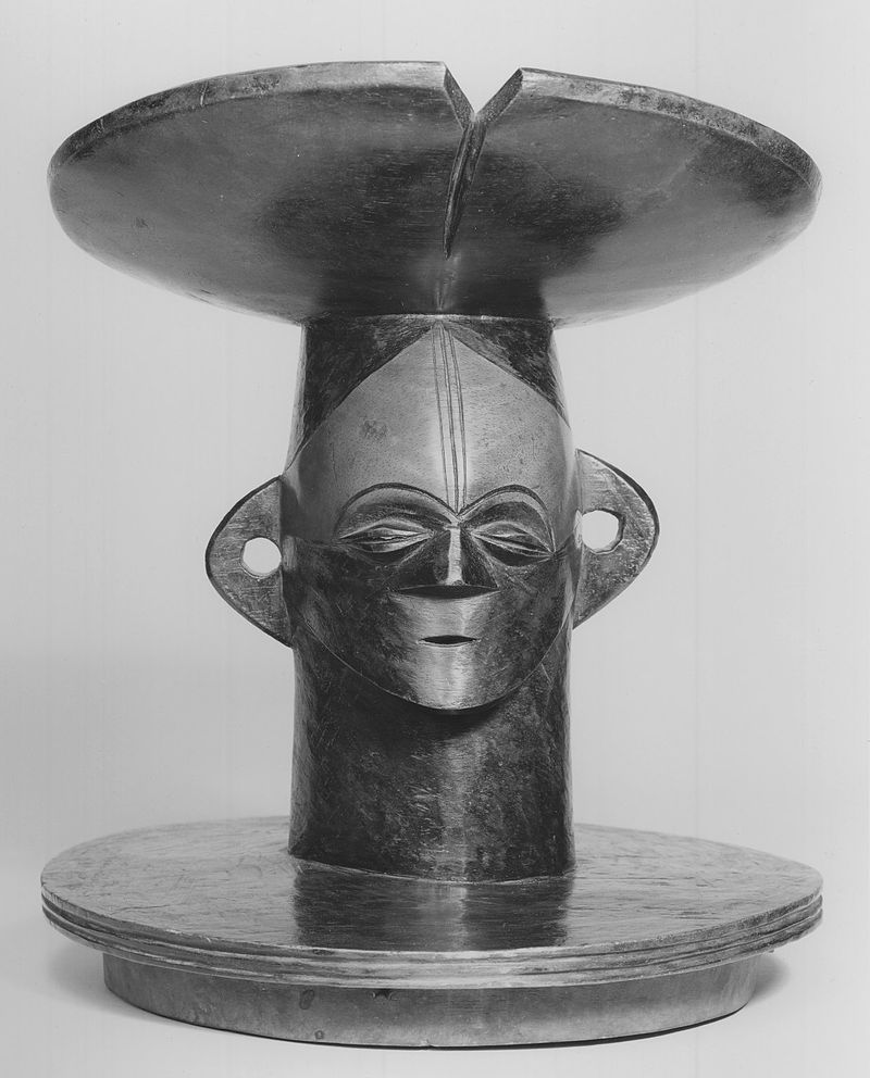 Lid with Figurative Head Description English: Carved darkwood container lid: carved cylindrical center section vertical as opposed to two horizontal elements above and below (hat and lid cover). Facial area at center has protruding ears (perforataed), slit eyes with crescent brows above, and nose with nostrils which blend into cheeks; mouth a small puntated slit. Incising lines vertically at forehead center: forehead area below 'hair' line and above eyes... C 19 27.9 x 22.9 x 22.9 cm