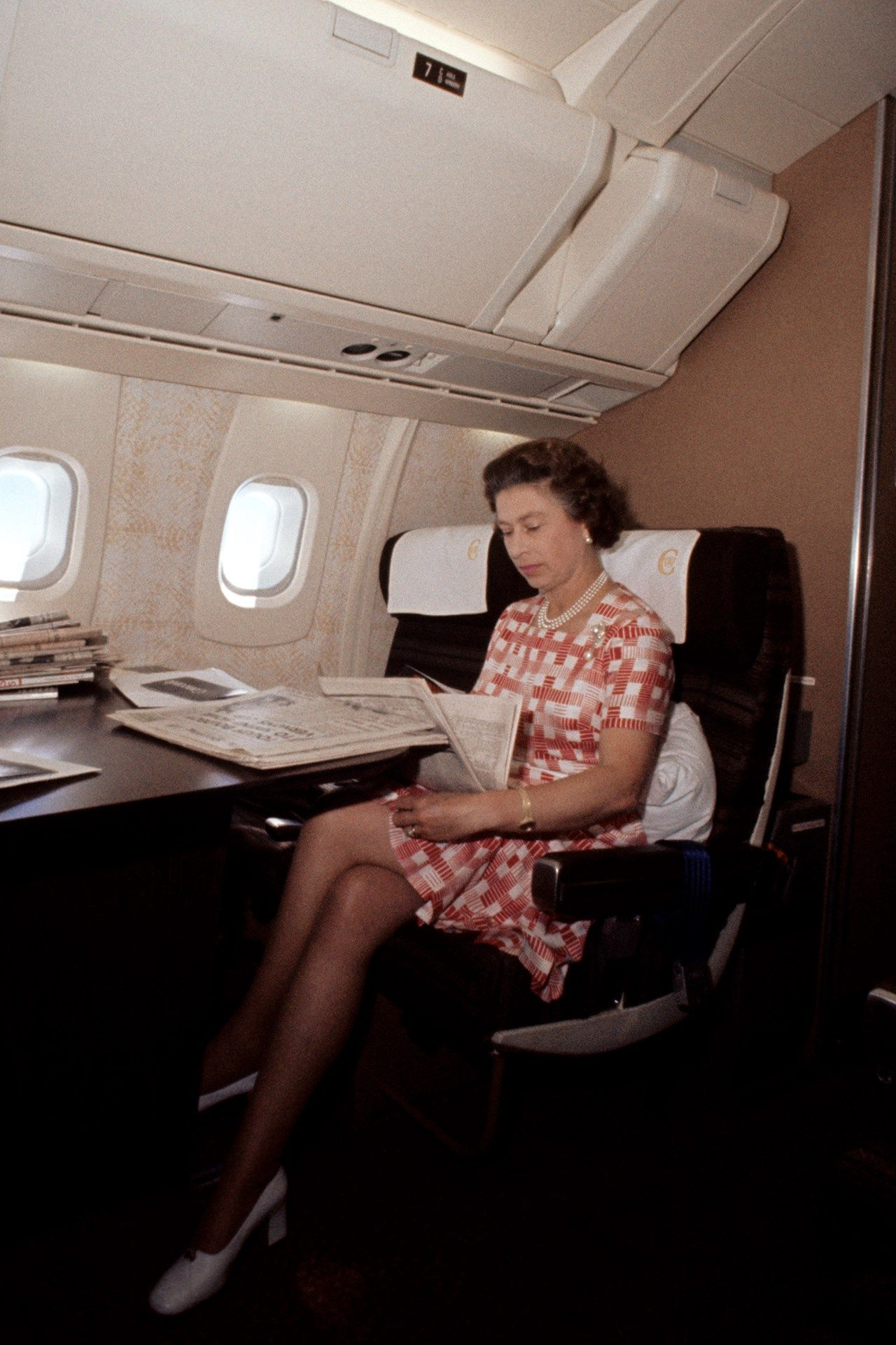 The Queen reading newspapers during her flight home from Bridgetown, Barbados, on Concorde after her Silver Jubilee tour of Canada and the West Indies, November 1977.