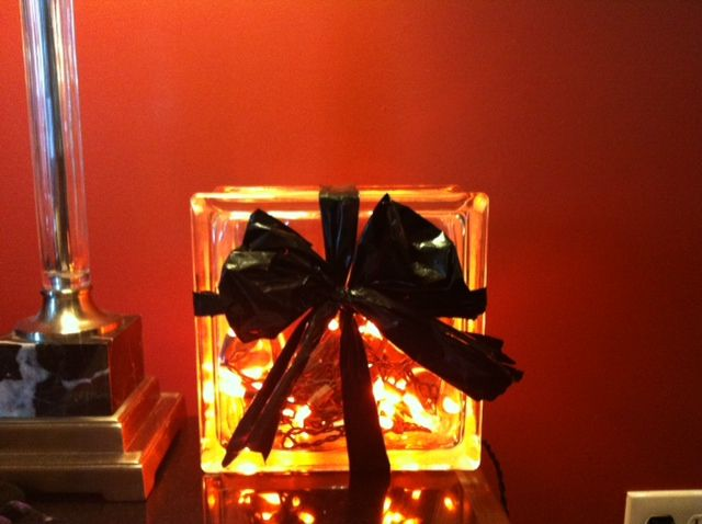 Made this using glass craft box - tapped in a hole and inserted halloween lights. Used heafty trash bag to make bow.