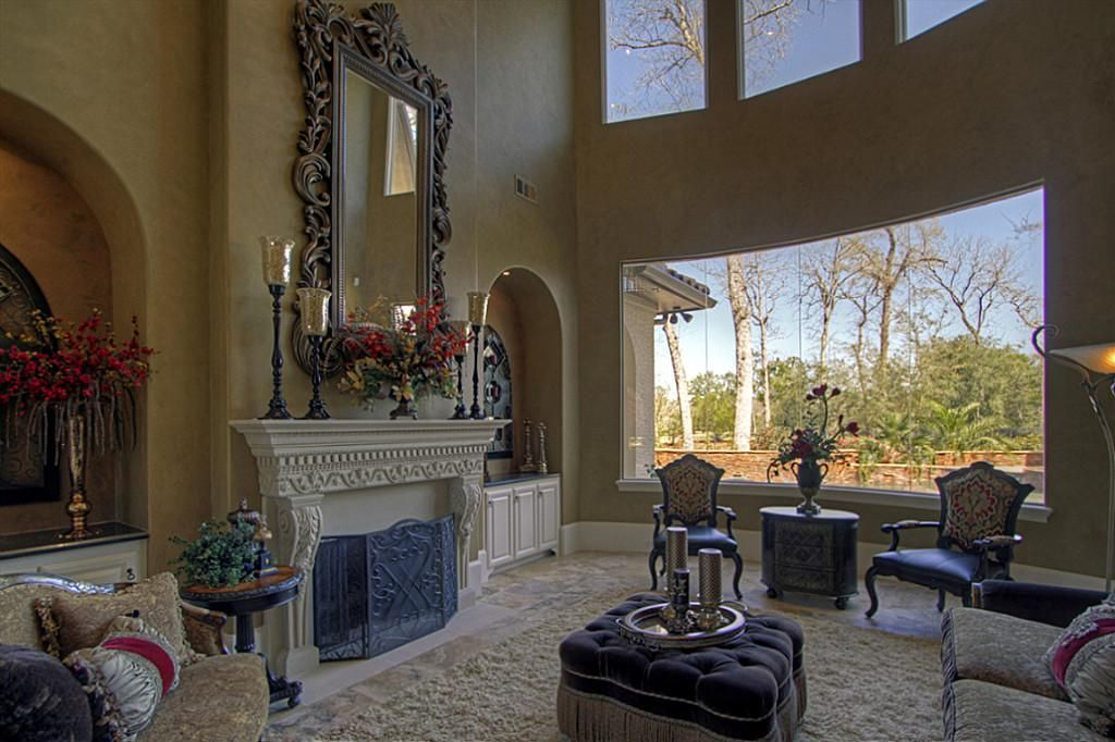 Sunken formal living room features butted glass windows ...