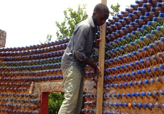 Homem constrói parte da casa com garrafas plásticas; Imagem Inhabitat