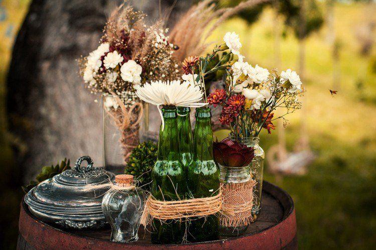 déco mariage champêtre - vases en bouteilles de verre avec des fleurs des champs blanches et rouges et épis de blé