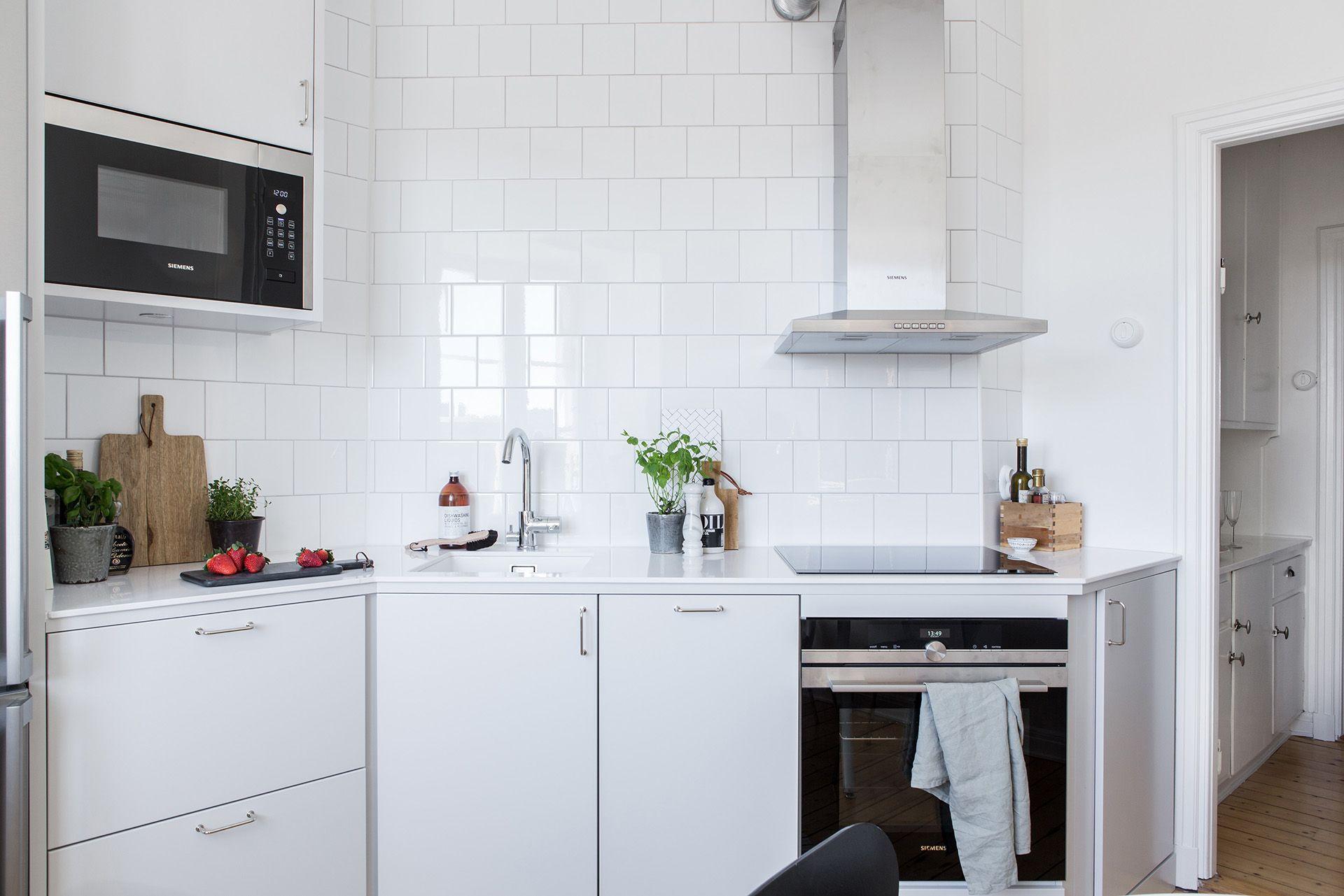Stilrent och minimalistiskt kök i sitt utförande Släta luckor i en snygg ljusgrå kulör, vitt