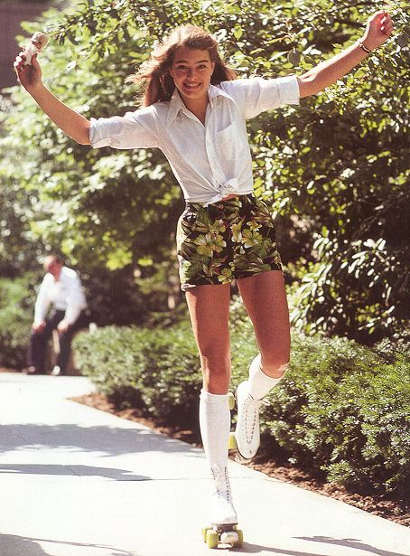 A young Brooke Shields roller skating in a tie-up blouse and printed high waisted shorts.