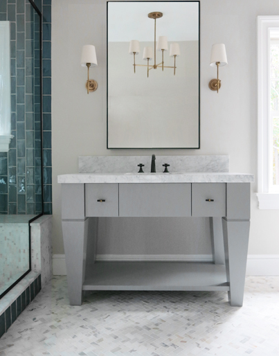 Exquisite bathroom features a gray washstand accented with for White bathroom cabinets with bronze hardware