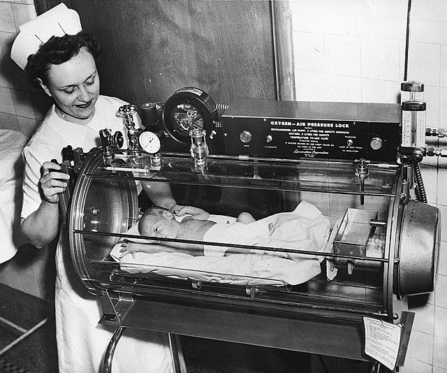 """St. Louis, Missouri: Two month old Linda Saffel, who weighed only two pounds 15 ounces at birth and now tips the scale at an ounce over five pounds, is ready to be taken home. But before leaving the DePaul Hospital, Baby Linda serves as """"model"""" in a demonstration by Nurse Genevieve Baker, of a new incubator-resuscitator which is already credited with saving three premature infants' lives since it was installed last November."""
