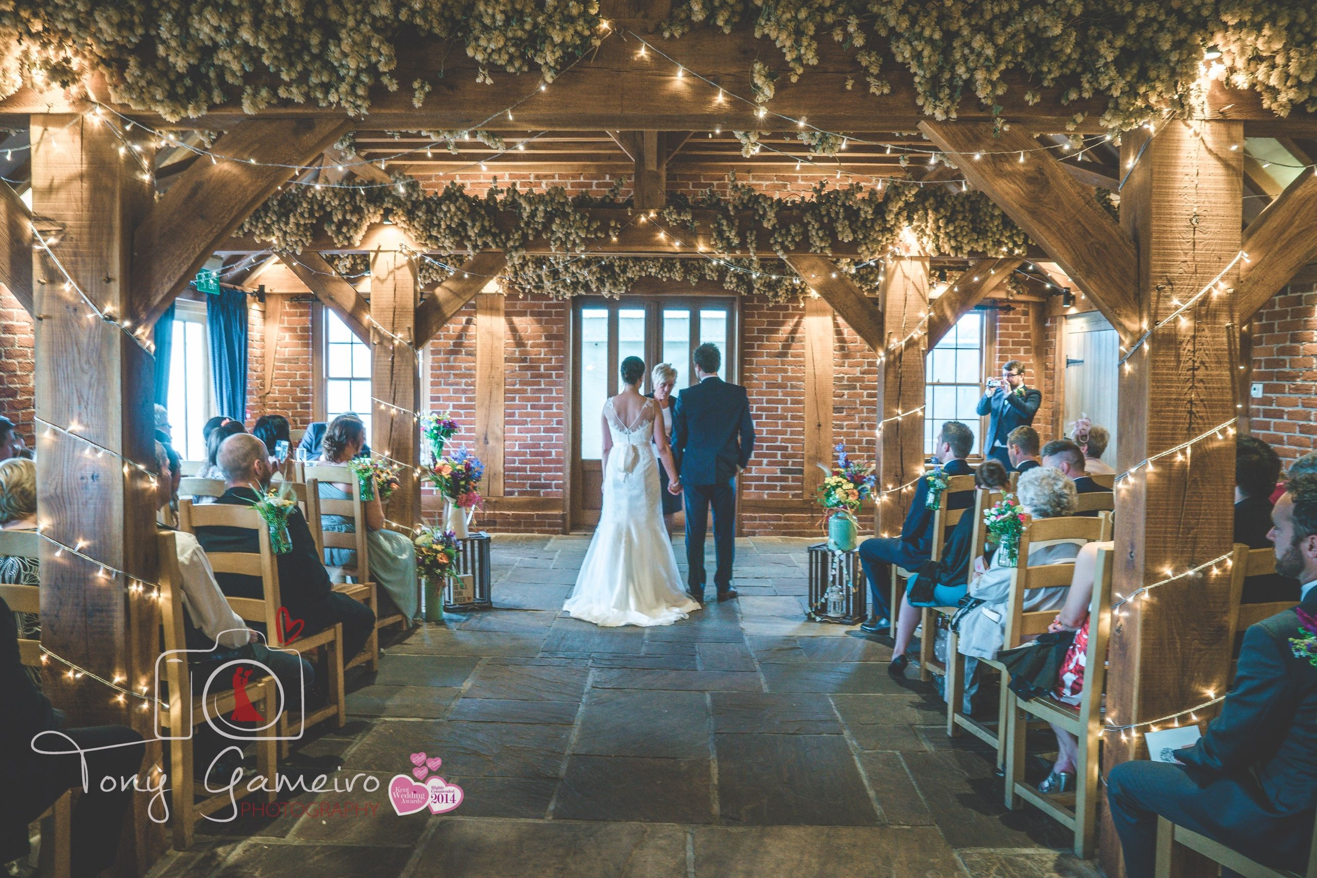 Ceremony In Our High Beam Barn Decorated With Colourful Flowers And Fairy Lights Kent Wedding Venue Www Theferryhouseinn Co Uk Barn Decor In