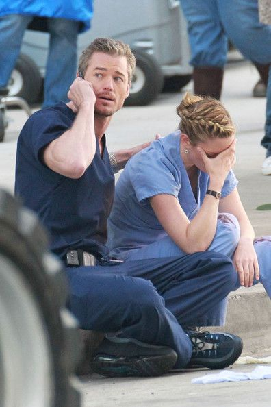 """Chyler Leigh Photos - Eric Dane consoles Chyler Leigh's character as the two film an emotional scene together for """"Grey's Anatomy"""" in Downtown LA. Dane, better known as """"McSteamy"""" on the show, is seen stretching in between takes and cozying up in a fleece sweater. Him and actress Chyler Leigh, who plays Dr. Lexie Grey, are seen sitting on a sidewalk together. Leigh is visibly crying and Dane consoles her by rubbing her back and making a phone call on his cell phone. Both actors are seen…"""