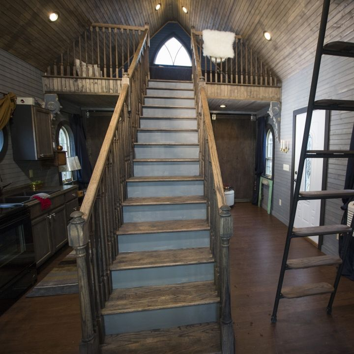 A grand staircase is the focal point of this medieval yet modern tiny home.